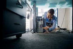 年轻对个人计算机的秘书连接的缆绳在办公室 免版税库存图片