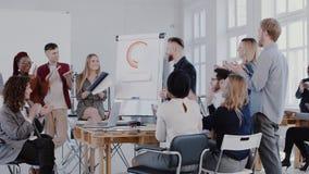 对中间年迈的上司商人的不同种族的商人拍手在研讨会以后在现代办公室,慢动作红色史诗 股票录像