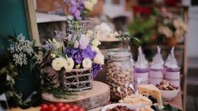 对乳酪桌的特写镜头视图 花、切片乳酪,坚果、鸡蛋、饮料和蕃茄在一个木板 股票视频