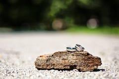 对人造白金在木装饰的婚戒在户外汽车白天形状  免版税库存照片