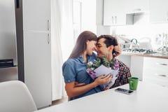 对他的女朋友的年轻人gifting的花束在厨房里 夫妇愉快拥抱 浪漫惊奇 库存照片