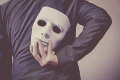 对他的表明企业欺骗和伪造企业合作的身体的商人运载的白色面具 免版税库存照片