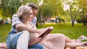 对他美丽的夫人的有同情心的人读书故事,轻轻地拥抱她,日期在公园 免版税库存图片