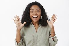 对令人惊讶的新闻说的激动的女孩 有卷曲发型的兴奋的健谈愉快的非裔美国人的妇女在时髦 免版税库存照片