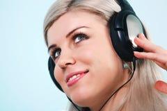 对佩带的妇女的耳机听的音乐 免版税库存照片