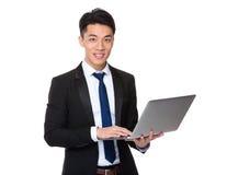 对便携式计算机的亚洲商人用途 库存照片