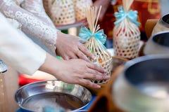 对修士的提议食物 新郎给施舍食物传统泰国婚礼的一个和尚 手一会儿投入了食物奉献物  免版税库存照片
