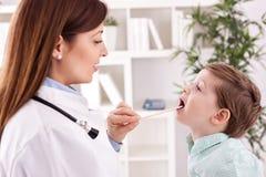对儿童患者的微笑的年轻医生审查的喉头 图库摄影