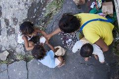 对光检查供营商妇女拥抱的婴孩和准备食物的囊从由传球手的孩子 免版税图库摄影