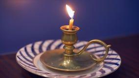 对光检查在站立在茶碟的烛台的燃烧在蓝色背景的桌上 股票录像