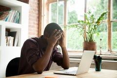 对公司危机失望的沮丧的黑人工作者 库存图片