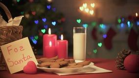 对关于桌的圣诞老人笔记在牛奶和姜曲奇饼附近,可爱的家庭传统 影视素材