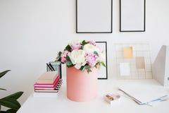 对办公室的花交付 工作空间、桌与笔记本和杂志 牡丹豪华花束在桃红色箱子的 库存图片