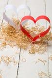 对华伦泰的日明信片s 白色和红色心脏由纸带做成 装饰卷曲刨花 库存照片