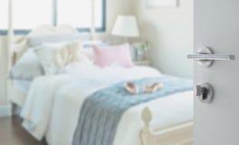 对卧室的被打开的白色门有枕头和玩偶的在白色床上 免版税图库摄影