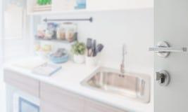 对厨房角落的被打开的白色门与在柜台的器物 免版税库存照片