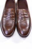 对反对白色背景的时髦的布朗便士游手好闲者鞋子 库存图片