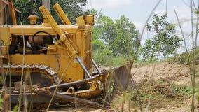 对取消地面的挖掘机平地机的未认出的工作者控制推土机 股票视频