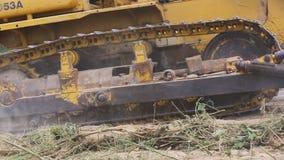 对取消地面的挖掘机平地机的未认出的工作者控制推土机 影视素材