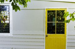 对后院小屋的黄色门在庭院里 免版税库存照片