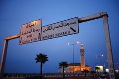 对哈桑二世清真寺的交通标志在微明期间在卡萨布兰卡,摩洛哥 免版税库存图片