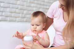 对哺养的婴孩牛奶瓶家的母亲尝试 库存图片