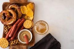对啤酒、巴法力亚香肠、芯片、brezels、薄脆饼干和芥末的快餐 oktoberfest的食物 图库摄影