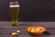 对啤酒在一块木板材,在玻璃的啤酒的薄脆饼干 免版税库存图片