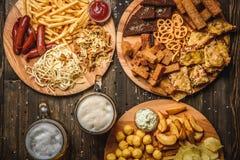 对啤酒的快餐在木背景顶视图 免版税库存照片