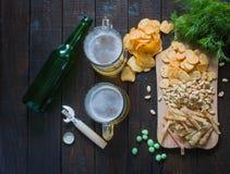 对啤酒的快餐,在一个木板和两个杯子啤酒,在一张木桌上 芯片,花生,鱼,薄脆饼干,莳萝,瓶 免版税图库摄影