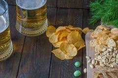 对啤酒的快餐,在一个木板和两个杯子啤酒,在一张木桌上 芯片,花生,鱼,薄脆饼干,莳萝 复制Spac 免版税库存照片