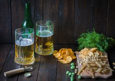 对啤酒的快餐,在一个木板和两个杯子啤酒 芯片,花生,鱼,薄脆饼干,莳萝,瓶 复制空间 免版税库存照片