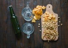 对啤酒的快餐,在一个木板和两个空的杯子,在一张木桌上 芯片,花生,鱼,薄脆饼干,瓶啤酒 库存照片