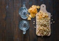 对啤酒的快餐,在一个木板和两个空的杯子,在一张木桌上 芯片,花生,鱼,薄脆饼干 与co的顶视图 库存照片