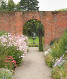 对围住的被成拱形的英国庭院网关 库存照片