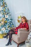 对圣诞树,红色礼服的美好的妇女网 免版税库存照片
