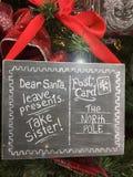 对圣诞老人的滑稽的圣诞节标志采取姐妹 免版税库存照片