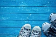 对在一个木板的女性和男性被佩带的运动鞋 库存照片