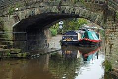 对在一座老桥梁旁边的英国驳船在河 图库摄影