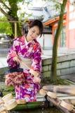 对在喷泉的竹杓子的年轻日本妇女用途 免版税库存照片