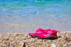 对在大理石Pebble海滩的桃红色游泳鞋子在绿松石海水旁边 海滩英国概念节假日护照夏天玩具 孩子鞋子为 免版税图库摄影