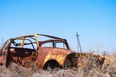 对在干燥干草中间的一辆黄色苏俄汽车的被放弃的残骸在南亚美尼亚 免版税图库摄影