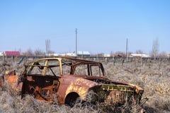 对在干燥干草中间的一辆黄色苏俄汽车的被放弃的残骸在南亚美尼亚 库存图片
