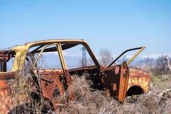 对在干燥干草中间的一辆黄色苏俄汽车的被放弃的残骸在南亚美尼亚 免版税库存图片