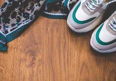 对在木背景的体育鞋子 新的运动鞋和空间广告文本的 免版税库存照片