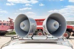 对在汽车屋顶的大减速火箭的扩音器 在背景的消防车 迫切或紧急公告概念 免版税库存照片