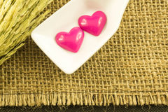 对在白色匙子的桃红色心脏,有米花的 免版税库存照片