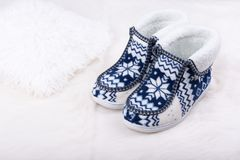 对在白色毛茸的地毯的温暖的女性拖鞋 免版税库存照片