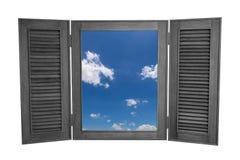 对在白色Backg隔绝的蓝天看法的被打开的木窗口 免版税库存照片