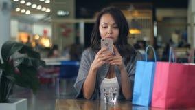 对在购物的手机的妇女用途在购物中心以后 库存照片